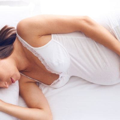 pregnant woman laying on side stock image